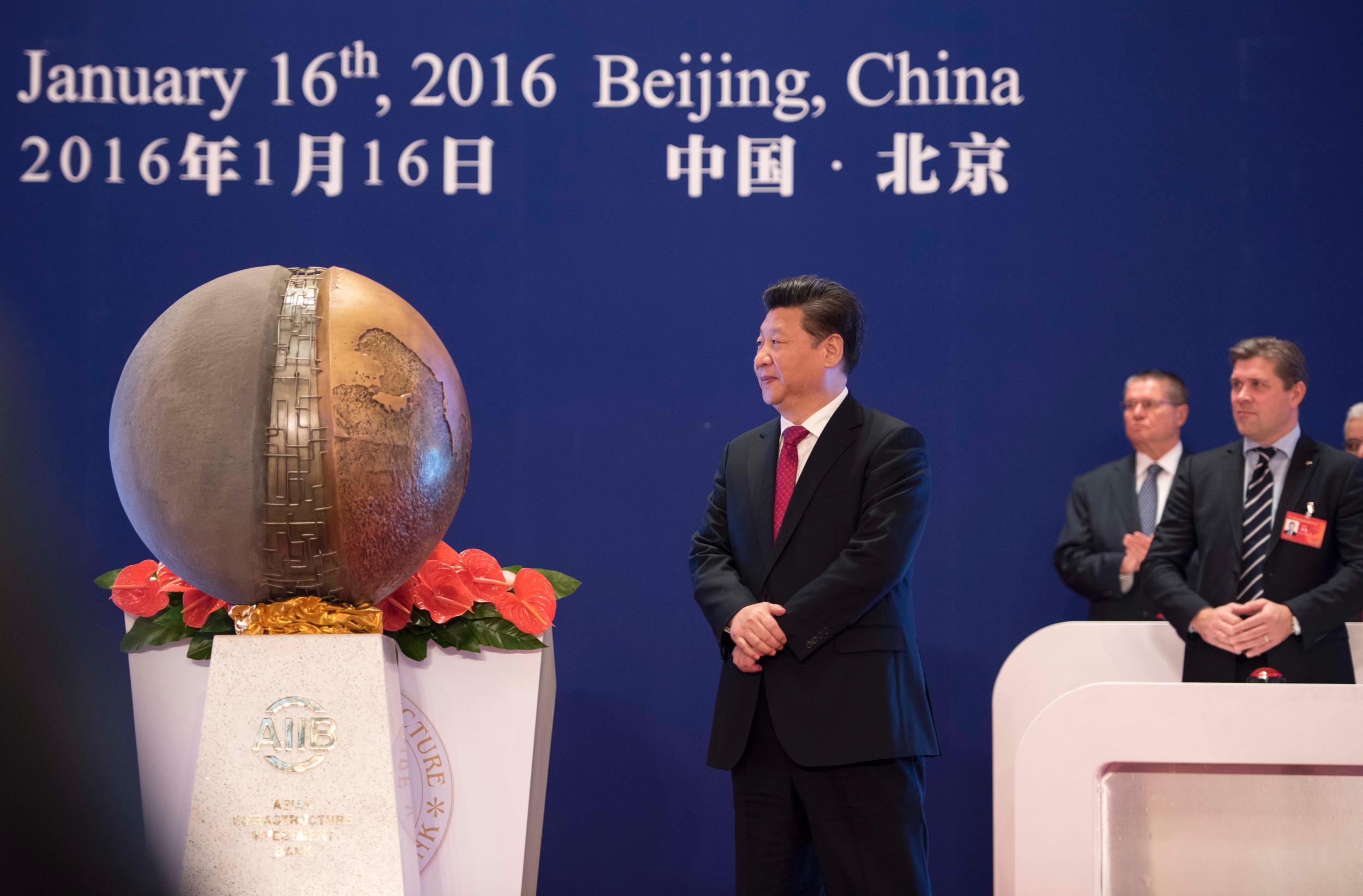 """2016年1月16日,亚洲基础设施投资银行开业仪式在北京举行。习近平主席出席开业仪式并致辞。这是习近平为亚投行标志物""""点石成金""""揭幕。"""